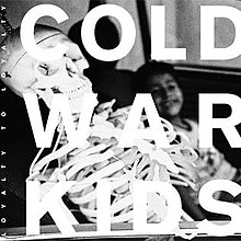 The cover features the band's logo in bold white letters. Behind the logo, there's a picture of a young boy and a skeleton with a screw on top of its head in the backseat of a vehicle.