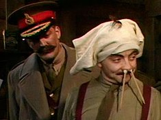 A man with a large moustache wearing a general's cap stands behind a man wearing underpants on his head and with pencils stuck in his nose.