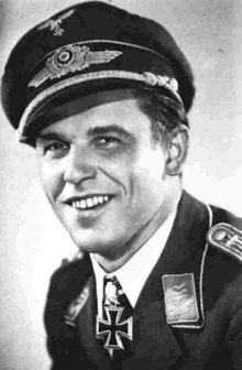 The head and shoulders of a young smiling man, shown in semi-profile. He wears a field cap and a military uniform, with an Iron Cross displayed at the front of his shirt collar.
