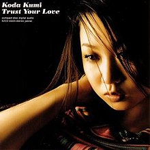 A close-up of a Japanese woman (Kumi Koda) with the song title and artists' name in the top left corner.