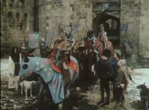 "The Black Adder - The series featured elaborate location shooting outside Alnwick Castle in Northumberland with horses, medieval-style costumes and a large cast of extras. In this scene from the opening of the episode ""Born to be King"", King Richard IV rides off to the Crusades, leaving Blackadder, Baldrick and Percy (front right) to plan a way to gain power."