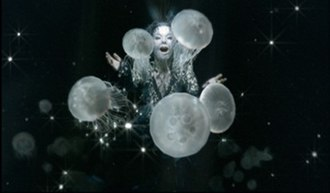 """Oceania (song) - Björk as """"Mother Oceania"""" in the music video, wearing tiny crystal beads on her face"""
