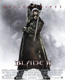Blade standing opposite his opponent, wearing his traditional jet black special suit and sunglasses, wielding his Titanium made, acid edged sword, with a negative background image around him showing the face of an evil vampire. Near the bottom are the film's name, credits and billing details. Wesley Snipes' name is written on the bottom.
