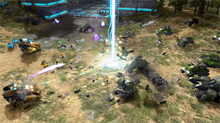 Units battle on a plain. On the left portion of the frame are curved, metallic vehicles and units of the Covenant. On the right are an assortment of human tanks—angular, accented with green. In the background are tall pine trees and a glowing alien structure.
