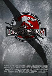 Film poster with a logo at center of a skeleton of a Spinosaurus, with its mouth wide open and hands lifted up. The logo's background is red, and right below it is the film's title. A shadow covers a large portion of the film poster in the shape of a flying Pteranodon, at the bottom of the image are the credits and release date.