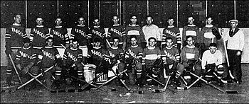 several men in hockey uniforms in two rows left to right on ice in
