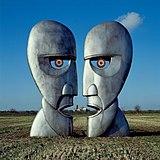Uma fotografia colorida de duas grandes esculturas de ferro cinza prateado de rostos opostos em silhueta.  As esculturas estão em um campo de trigo marrom com um céu azul atrás delas.