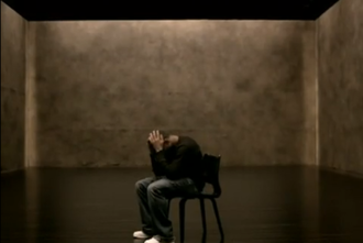 Confessions Part II - Usher isolated in a low lighting room, sat on a chair.