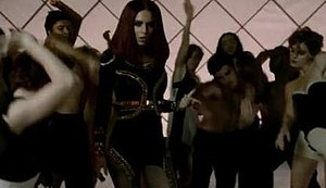"""3 Words (song) - A frame from the """"Egyptian-themed"""" scene in the middle and end of the video, where Cole wears a brunette wig and dances with backing dancers."""