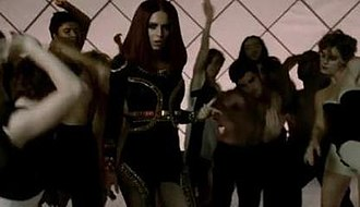 "3 Words (song) - A frame from the ""Egyptian-themed"" scene in the middle and end of the video, where Cole wears a brunette wig and dances with backing dancers."