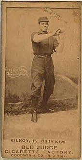 A baseball card of a man in a dark baseball uniform wearing a matching baseball cap and holding his hands in the air in front of his chest.