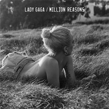 Lady Gaga lies in a field of grass in this black and white photograph.