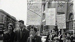 A group of young people with placards supporting boycott on the street. Behind them on the upper right is a portion of a large stone building, on the upper left the upper floors of a terrace. Behind the people, at street level, motor cars and buses can be seen.