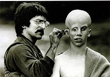 Savini, on the left, applies make-up behind Lehman's ear. Lehman's bald head has been made to appear over-large; his eyes point in different directions, and his teeth are extremely crooked.