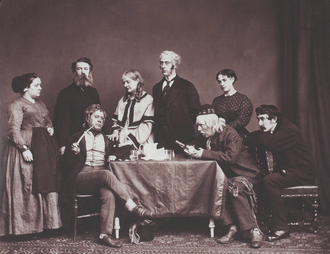 Stage photograph showing group of 3 women and five men in everyday Victorian clothes