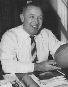 Dick Gallagher sitting at a table with a football in his hands in 1959