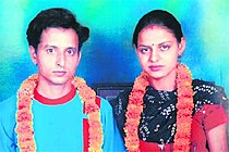 Newlyweds garlanded with marigolds