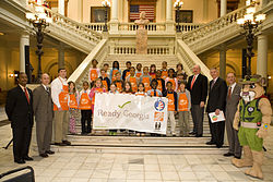 Governor Perdue, GEMA director Charlie English, ReadyKids mascot Rex the mountain lion, and Georgia elementary school students pose with a banner at Ready Georgia's official launch