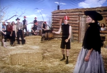 A  man wearing a black turtleneck and a red hat holds a whip while a woman in a black dress smoking a cigarette with a holder stands in front of him. In the background are onlooking cowboys and cowgirls, four men wearing black turtlenecks playing instruments, and a ranch house.