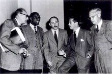 Five well-dressed men standing and conversing.