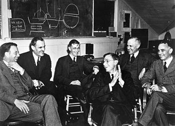 Eine Gruppe von Männern in Anzügen sitzt herum und lacht.  Auf der Tafel dahinter befindet sich ein weggeworfener Plan zum Zusammenbau eines Urankerns.