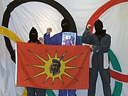 Members of the Native Warriors Society pose with the stolen Winter Olympics flag. They stole the flag to protest the Olympics, and to honour the death of Harriet Nahanee.