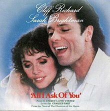 A photograph displaying Cliff Richard laying his right arm over the shoulder of Sarah Brightman.