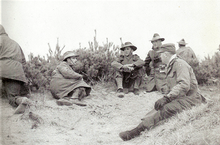 Four caucasian soldiers in uniform sitting on the ground talking. Three of the men are wearing slouch hats, while the fourth is wearing a cap.