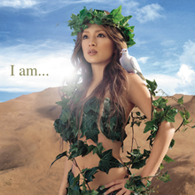 "Ayumi Hamasaki shown from the waist up, looking outward with her hands on her waist, wearing only foliage, with a dove resting on her left shoulder. In small text, ""I Am..."" is written on the left side."