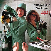 """Weird Al"" Yankovic dressed as a surgeon holding a chainsaw in his hand, flanked by a woman dressed like Madonna and wearing sunglasses, also in surgeon's uniform."