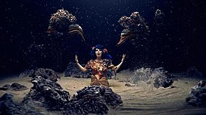 Mutual Core - A screenshot from the music video where Bjӧrk sings surrounded by rocks under a rain of ashes.