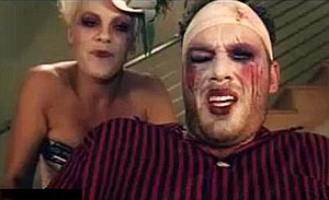 Please Don't Leave Me - Pink pushing her boyfriend, while he is in a wheelchair, dressed as a clown.