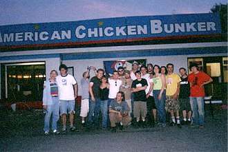 """Poultrygeist: Night of the Chicken Dead - The crew of Poultrygeist stands before the """"American Chicken Bunker"""". Director Lloyd Kaufman is on the far left."""
