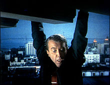 A man, seen from mid-chest up, hangs by his hands from the edge of an apparently tall structure, gazing down in fear. He is wearing a dark suit and an orange tie with a clip; in the distance behind him is a cityscape at night or in the early morning. There is a bluish cast to the background.