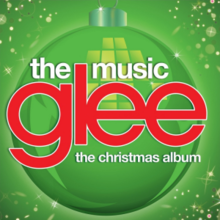 "The word ""Glee"" is in large lowercase red print and centered on a green background with a Christmas bauble. Beneath it are the words ""The Christmas Album"" and above are ""The Music"", both in lowercase white font."
