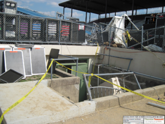 Indiana State Fair stage collapse - One of the Jersey barriers used as ballast for the stage roof guy lines after it was pulled down a flight of stairs by the collapsing stage (background). The lack of resistance provided by these barriers was found to be the primary cause of the collapse.