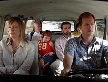 A film screenshot shows the family all seated in the Volkswagen Microbus as it is driven on a highway. The angle is from the windshield looking into the vehicle so that the majority of the interior can be seen. The mother is sitting in the front passenger seat with a dull expression on her face. The father is driving the vehicle with a similar expression. In the middle row, the daughter is looking down, listening to music from a CD player. Her uncle is seated on the right, looking to his left. In the back row, the grandfather is looking towards his grandson (whose face is slightly obscured by his father's head due to the angle). In the background, other vehicles can be seen driving on the highway.