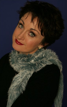 A close-up posed upper body shot of a woman. Her head is tilted to her left. She has short, black hair and pale blue eyes. She wears a grey/white fleecy boa/scarf over her black top. She has make up and red lipstick and sports an earring in her left ear (right ear is not visible).