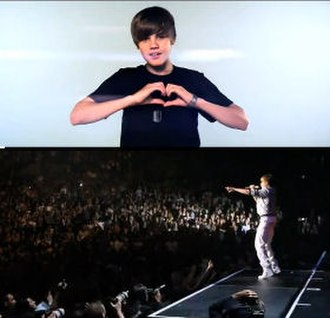 Love Me (Justin Bieber song) - Bieber making a heart with a blue background relative to the songs theme. Bieber seen performing in front of a large crowd.