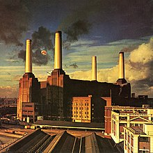 An image of the Battersea Power Station in England, where a giant pig can be seen flying between its left chimneys.