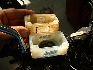 Polymer - A plastic item with thirty years of exposure to heat and cold, brake fluid, and sunlight. Notice the discoloration, swelling, and crazing of the material