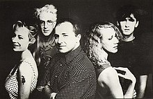 Five adults framed in upper body. In the front row, the left female is shown in left profile, slightly turned to her left and smiling, she wears a white dress with black polka dots and has a serpent tattoo on her upper left arm. Behind her, a slightly balding male is more turned towards the front and has his arms folded across his chest, his shirt is dark with white polka dots. Back to back to him is the second female in right profile with her right arm touching her shoulder. In the back row, the left male has white hair and is facing forward, he is wearing glasses and has an obscured design on his shirt. The right male has dark hair, he is staring forward and wears a black tee shirt.
