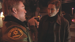 A man in a sheriff's uniform is talking to a man with black hair dressed in brown jacket. The film quality is deliberately low-quality.