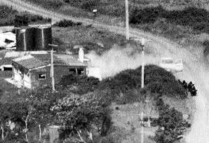 Aramoana massacre - Anti-Terrorist Squad officers crouch on Muri Street (right), before storming Gray's beach house (left)