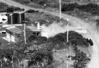 Aramoana massacre - Anti-Terrorist Squad officers crouch on Muri Street (right), before storming Gray's beach house (left)