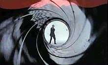 The figure of silhouetted man points a gun straight at the camera.