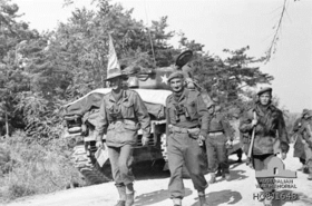 Two men in uniform walking along a road, the man on the left is wearing a slouch hat and holding a map, while the man on the right is wearing a beret. Both men binoculars around their necks. In the background is a stationary tank on the side of the road and a number of armed soldiers.