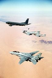 Portrait photography of four aircraft overflying orange desert and almost-flat terrain; horizon is blurred. Leading is black aircraft, followed by two single-engine jet aircraft, the one closer to camera being refueled by leading jet via a stiff hose connecting the two. Closest jet to camera is pale gray, has two engines and vertical fins, flying with wings unswept.