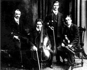 four musicians with string instruments in a posed group photograph