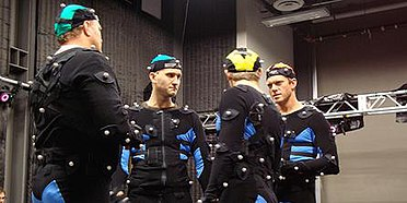 Four actors talking in motion capture suits (black full-body suits, and a small cap upon the head, with small white balls), in a studio.